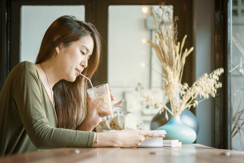 Closeup asian woman reading a book and drinking iced chocolate at the wooden counter desk in coffee shop with happy face on blurre royalty free stock photo