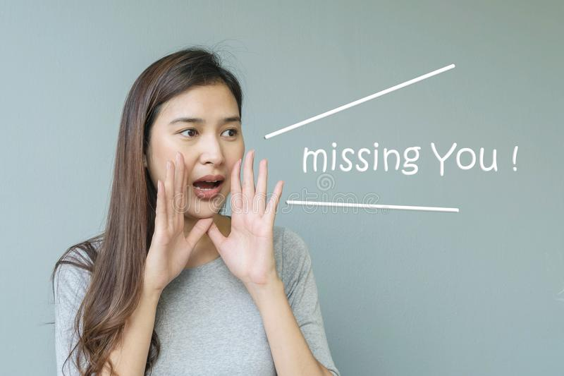 Closeup asian woman in shout action with missing you word on blurred cement wall textured background with copy space royalty free stock photo