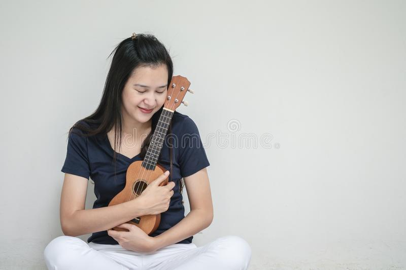 Closeup asian woman with ukulele on white cement wall texture background royalty free stock images