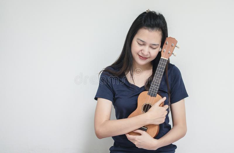 Closeup asian woman with ukulele on white cement wall texture background royalty free stock photography