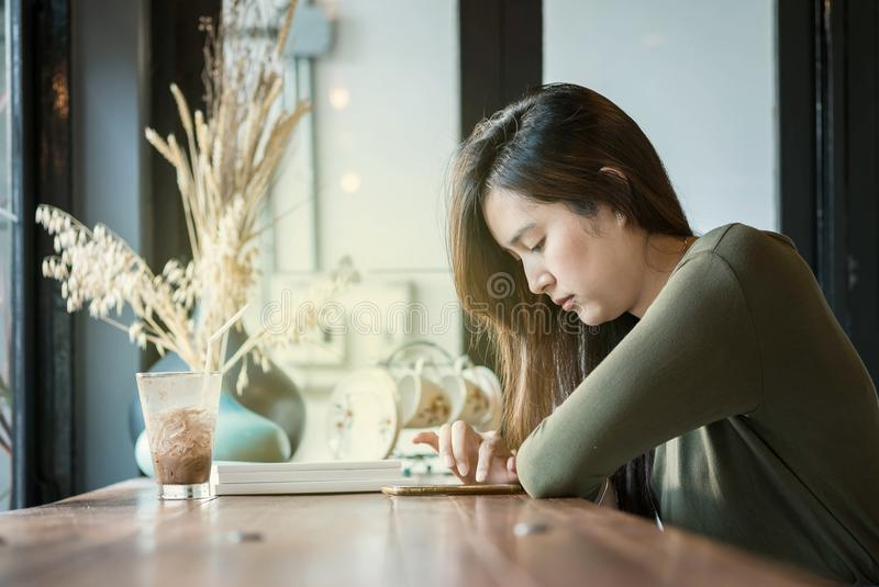 Closeup asian woman use smartphone for read online news at the wooden counter desk in coffee shop on blurred coffee shop view back royalty free stock photography