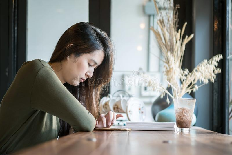 Closeup asian woman use smartphone for read online news at the wooden counter desk in coffee shop on blurred coffee shop view back. Closeup woman use smartphone royalty free stock photo
