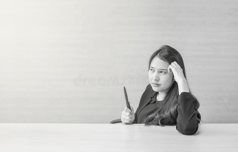 Closeup asian woman working with thinking face and a pen in her hand on blurred wooden desk and wall textured background in the royalty free stock photo