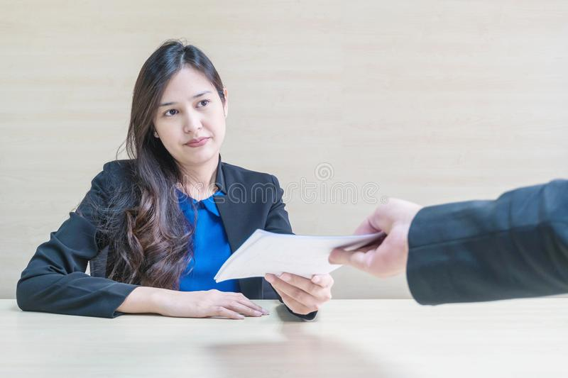 Closeup asian working woman receive work document from her boss with unwilling face in meeting room on blurred wooden desk and stock photography
