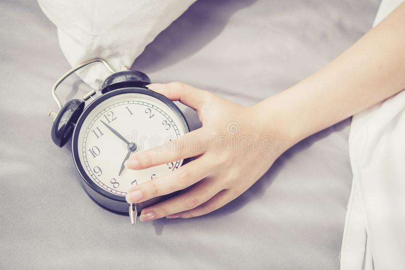 Closeup asian young woman turn off alarm clock in good morning, wake up for sleep with girl holding alarm clock. Time and lifestyle concept stock image