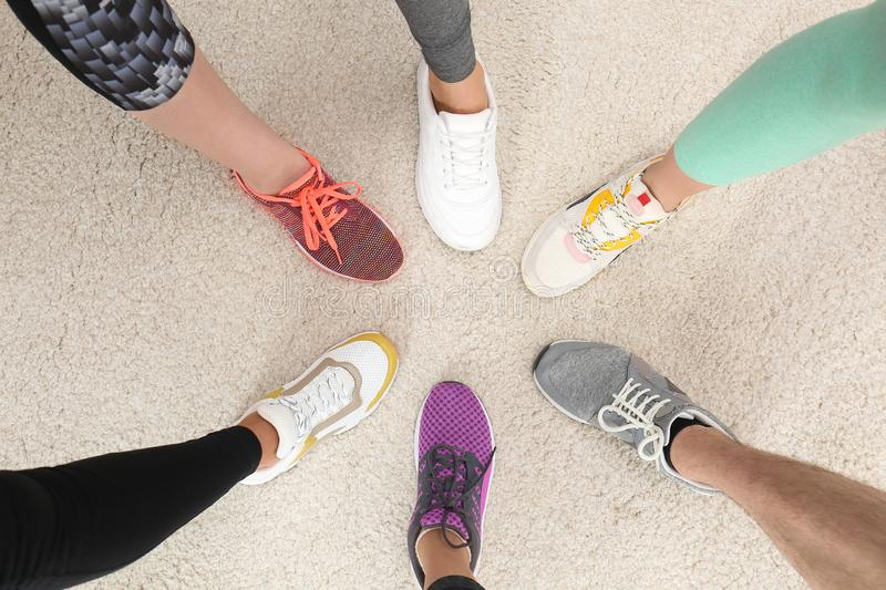 Closeup of athletes wearing sports shoes and standing in circle on beige carpet stock images