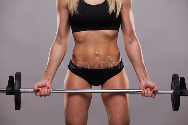 Closeup athletic torso of woman in sporty cloths. She is holding a barbell on grey background with copyspace stock photo