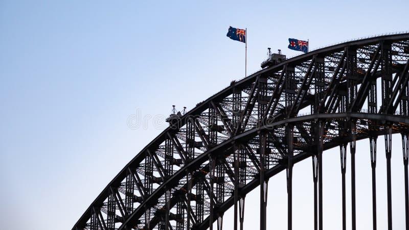 Closeup av överkanten av Sydney Harbour Bridge med att vinka australiska flaggor arkivfoton