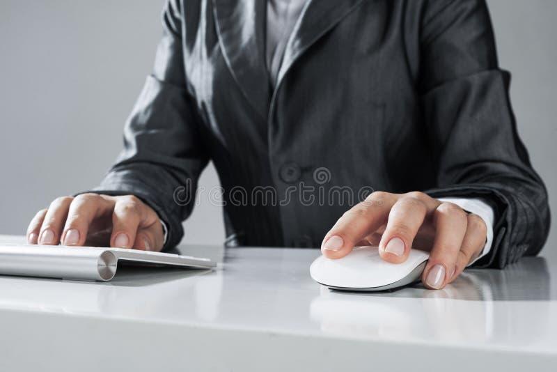 Closeup av affärskvinnahandmaskinskrivning på tangentbordet med musen på w royaltyfri foto