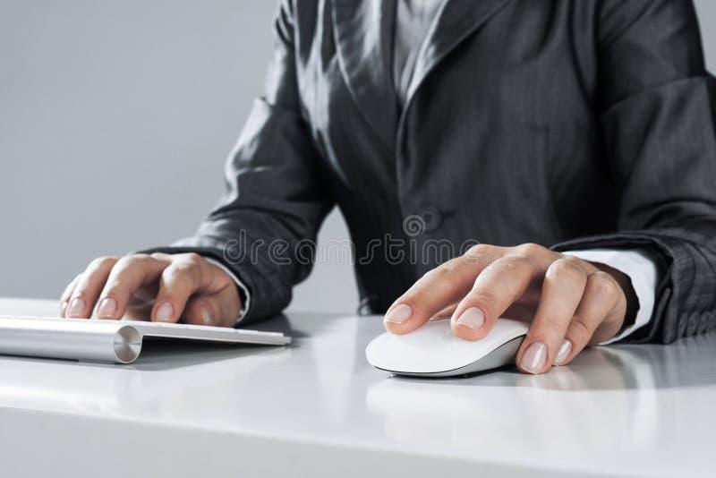Closeup av affärskvinnahandmaskinskrivning på tangentbordet med musen på w arkivbild