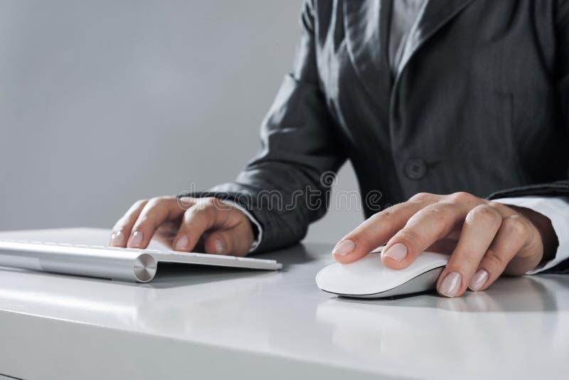 Closeup av affärskvinnahandmaskinskrivning på tangentbordet med musen på w arkivfoton