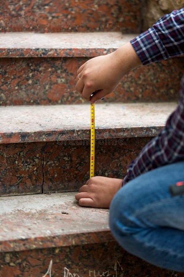 Closeup av arbetaren som mäter höjd av stenmoment arkivbilder