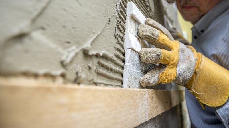 Closeup av arbetaren som placerar försiktigt en dekorativ tegelplatta i a royaltyfria bilder