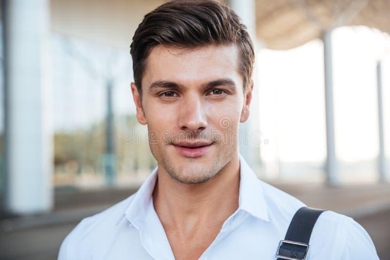 Closeup av att le den unga affärsmannen i den stående vita skjortan utomhus royaltyfri bild