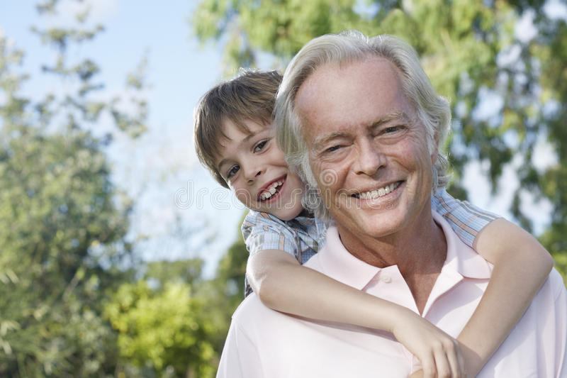 Closeup av att le farfadern med sonsonridning på ryggen arkivfoto