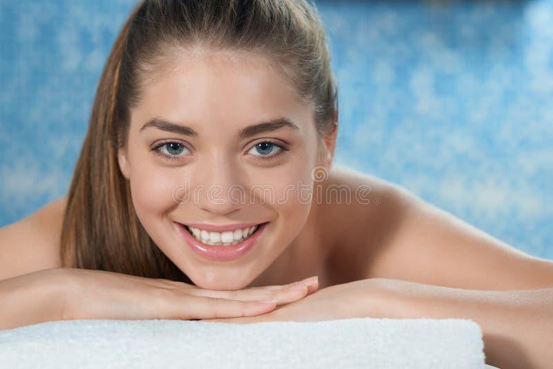 Closeup av att le kvinnan som ligger på magen på soffan i brunnsort fotografering för bildbyråer