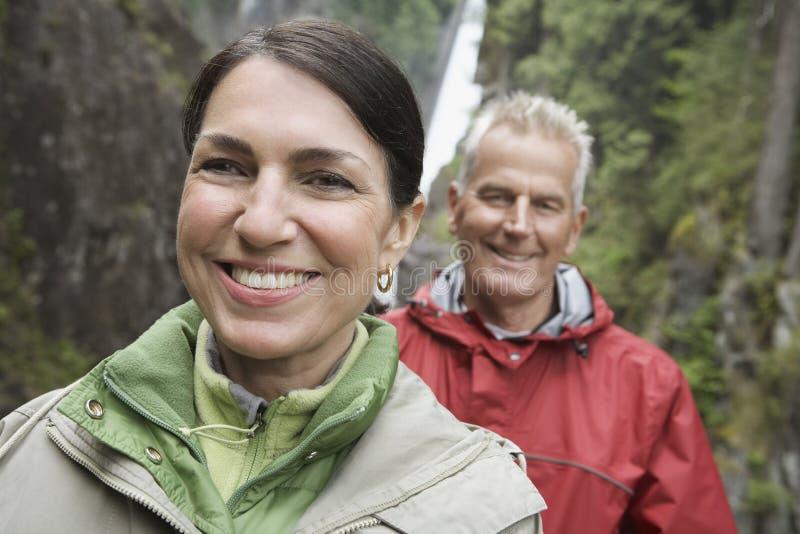 Closeup av att le par mot vattenfallet royaltyfri foto