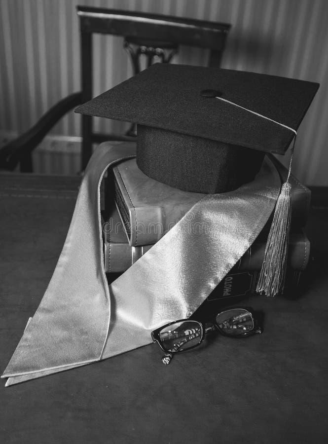 Closeup av avläggande av examenhatten i bandet som ligger på högen av böcker royaltyfria foton