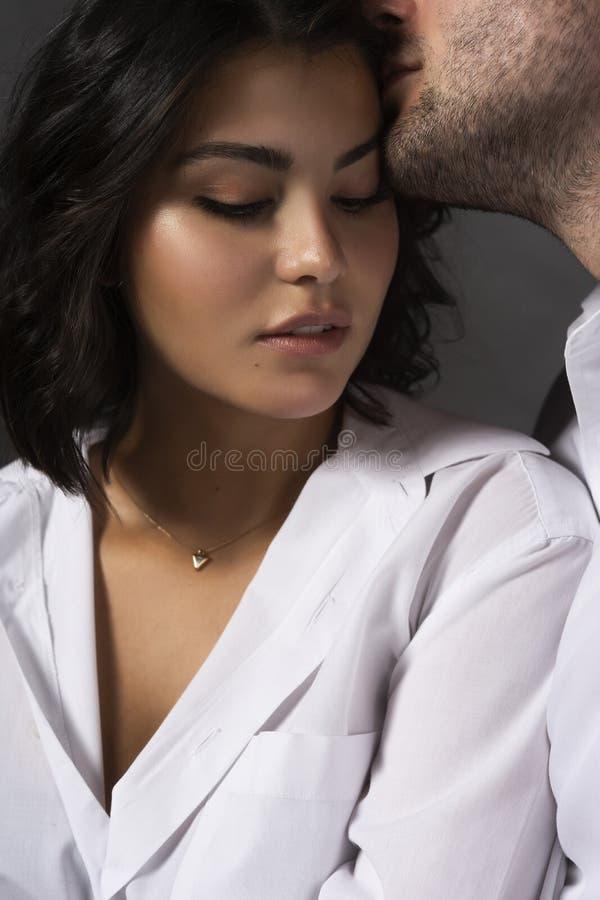 Closeup av bärande vita skjortor för ett härligt par En man trycker på passionately hans kanter till flickans hår Tillfällig inne royaltyfria bilder