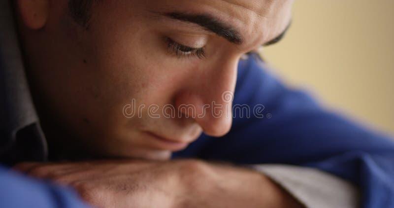 Closeup av bekymrat latinamerikanskt mansammanträde på skrivbordet arkivfoton