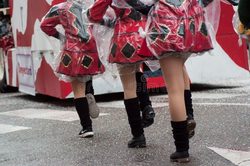Closeup av ben för pompomflickor som bär med sockor och mini- röda kjolar som ståtar i gatan royaltyfria foton
