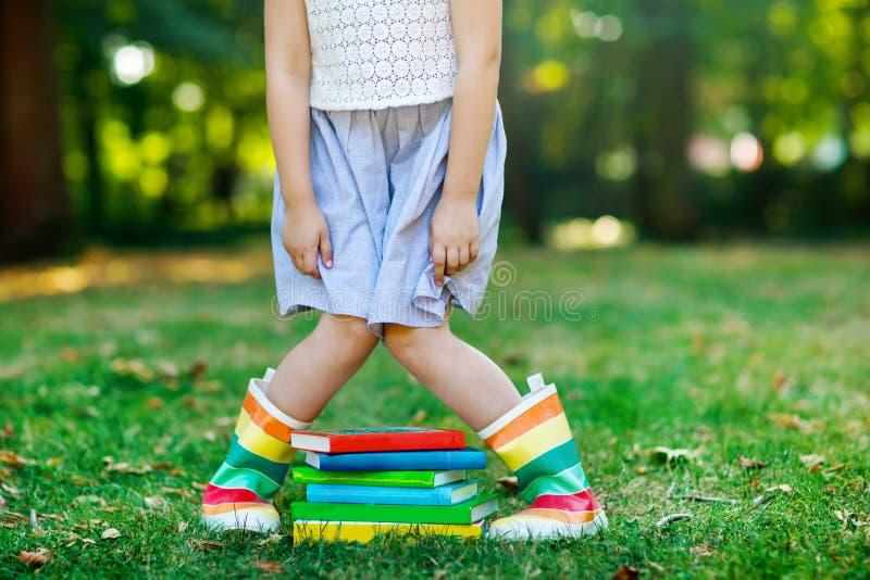 Closeup av ben av skolaflickan i gummistöveler och olika färgrika böcker på grönt gräs första dag till skolan eller royaltyfria foton