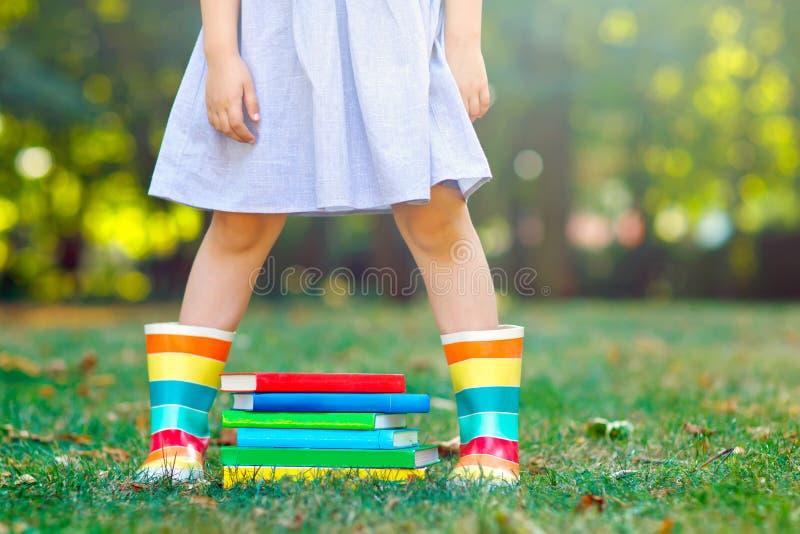 Closeup av ben av skolaflickan i gummistöveler och olika färgrika böcker på grönt gräs första dag till skolan eller royaltyfri foto