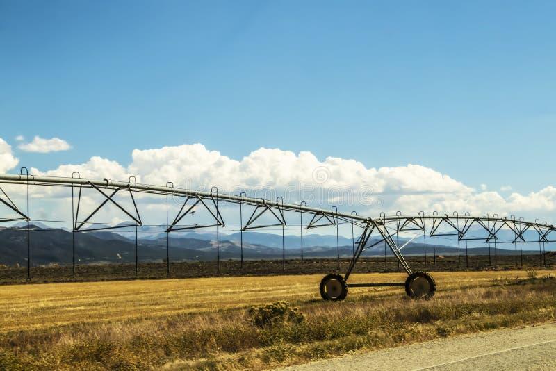Closeup av bevattningsystem för lantgårdledning i vägrenfält med berg i avstånd och härlig blå himmel med moln arkivbilder