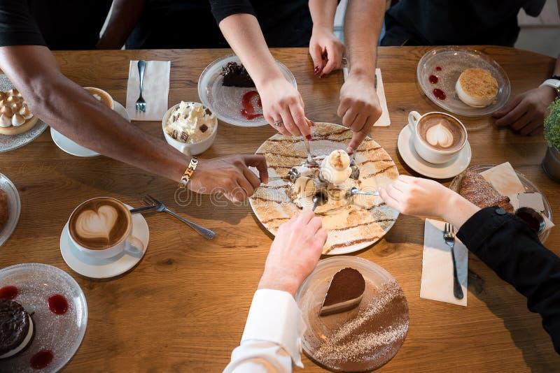 Closeup av blandras- h?nder med efterr?tter och kaffekoppar i ett kaf? royaltyfria bilder