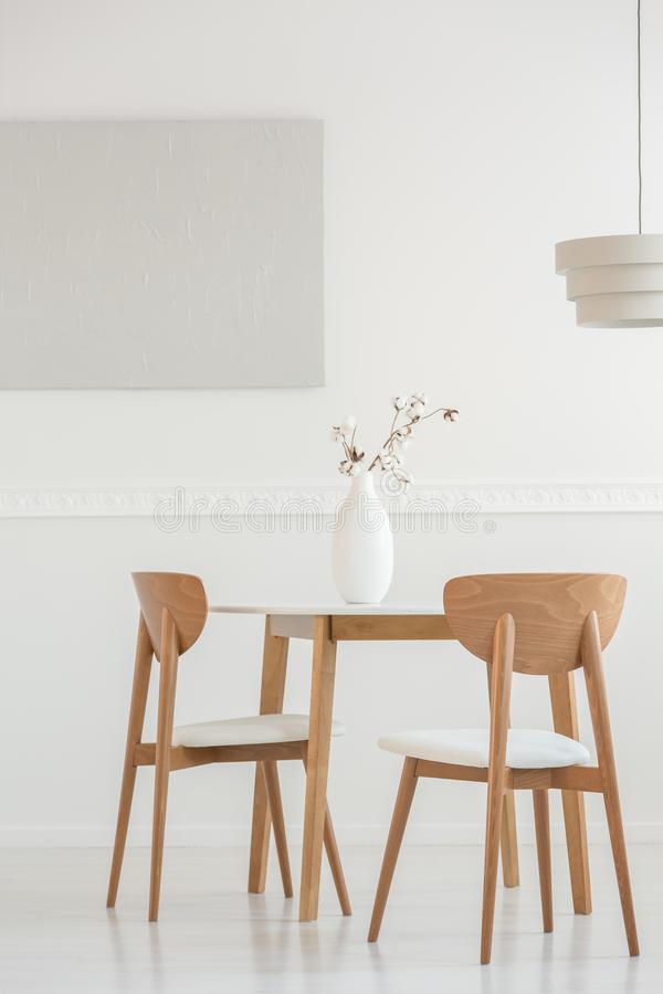 Closeup av blommor i den vita vasen p? den tr??ta middag tabellen med stolar fotografering för bildbyråer