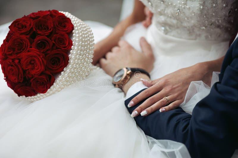 Closeup av bruden i en elegant vit klänning och med en rosbouque royaltyfria foton