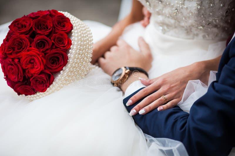 Closeup av bruden i en elegant vit klänning och med en rosbouque royaltyfri foto