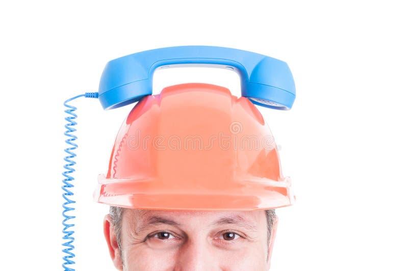 Closeup av byggmästaren som rymmer den retro mottagaren på hjälm arkivfoton