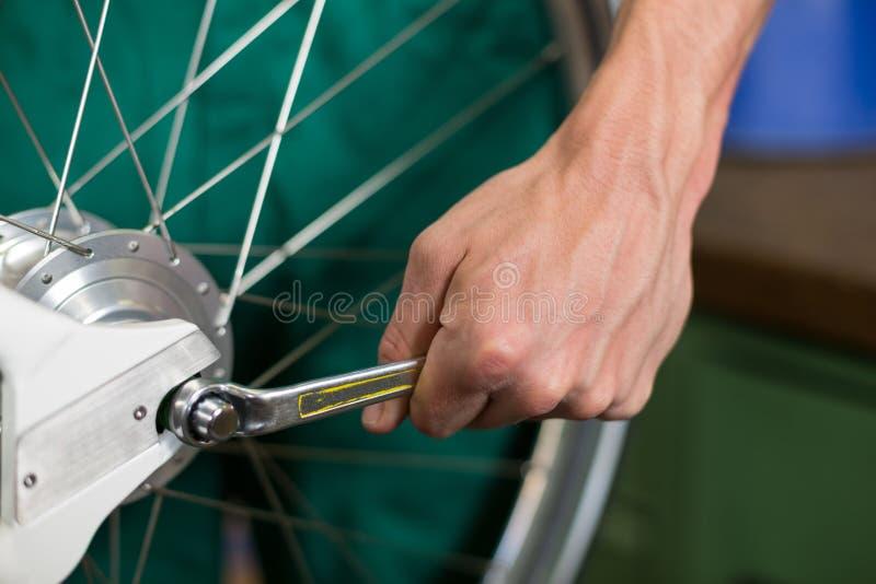 Closeup av cykelmekanikern med en skiftnyckel royaltyfri foto
