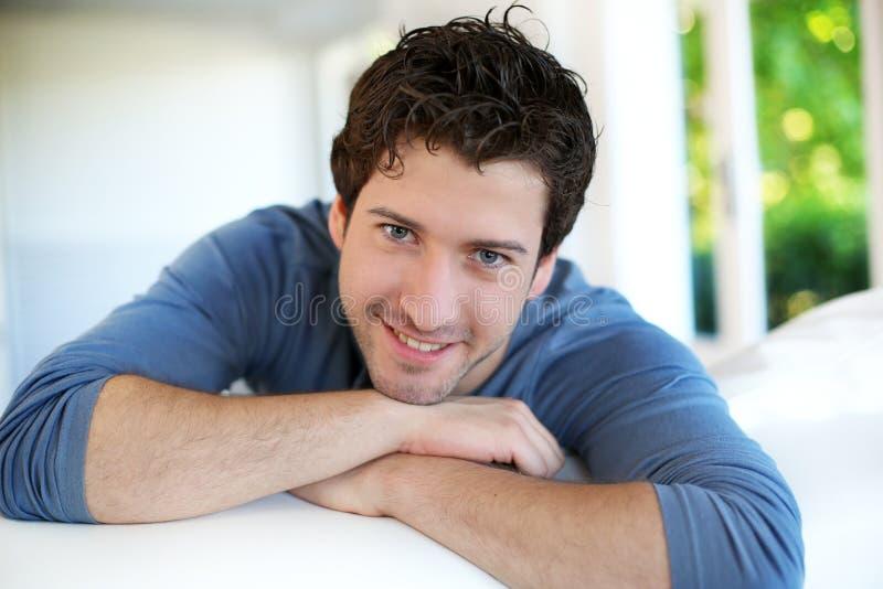Closeup av den attraktiva benägenheten för ung man på soffan royaltyfri fotografi