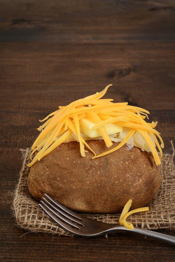 Closeup av den bakade potatisen med smör och ost arkivbilder