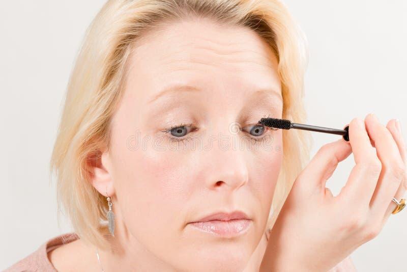 Closeup av den blonda damen Applying Mascara Make-Up arkivbilder