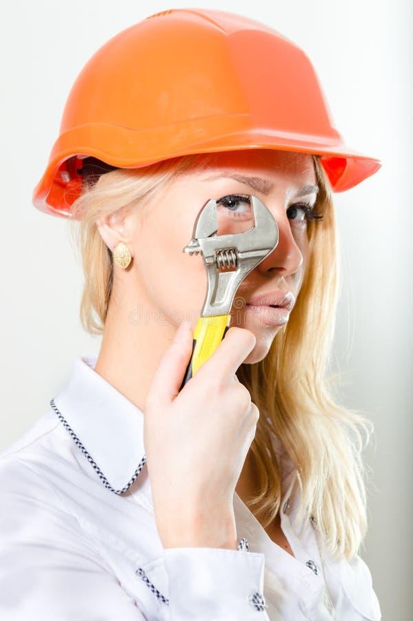 Closeup av den blonda kvinnan med byggmästarehjälmen & skiftnyckeln arkivfoton