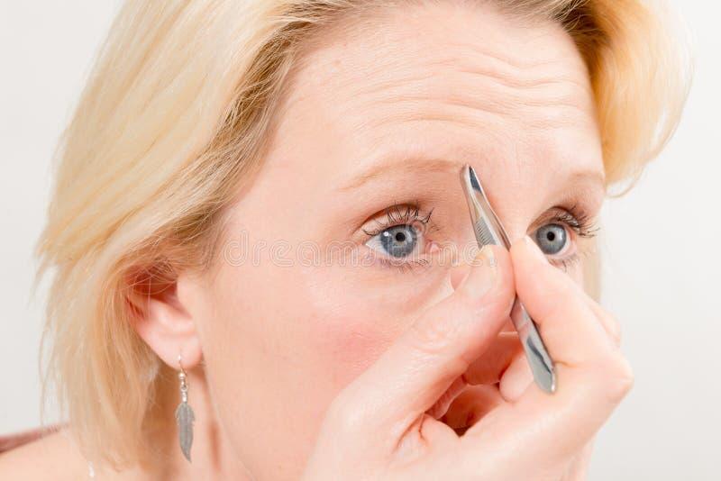 Closeup av den blonda kvinnan som plockar hennes ögonbryn royaltyfria foton