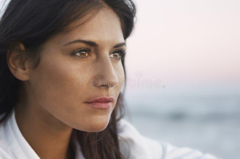Closeup av den fundersamma kvinnan som bort ser på stranden royaltyfri bild