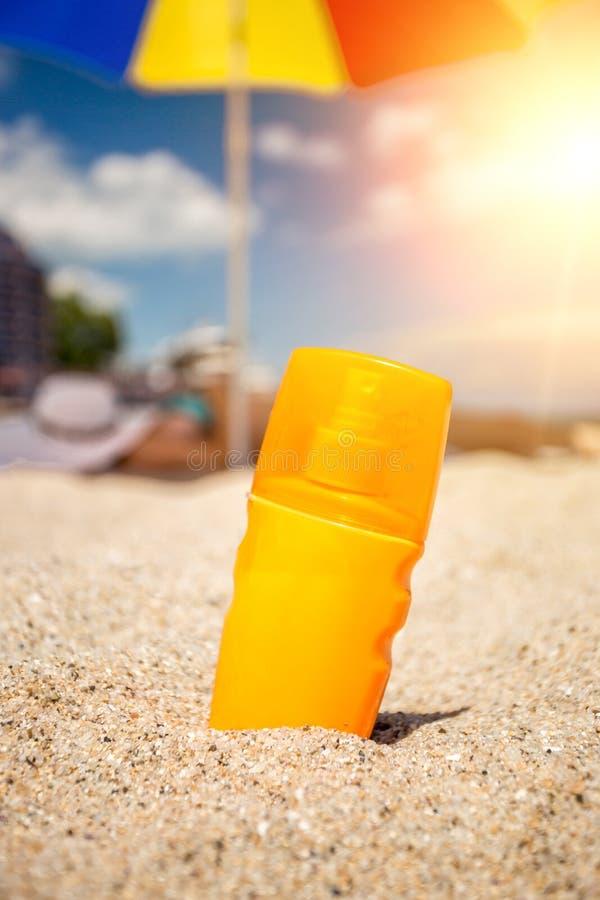 Closeup av den gula solkrämflaskan som ligger på sand på stranden fotografering för bildbyråer