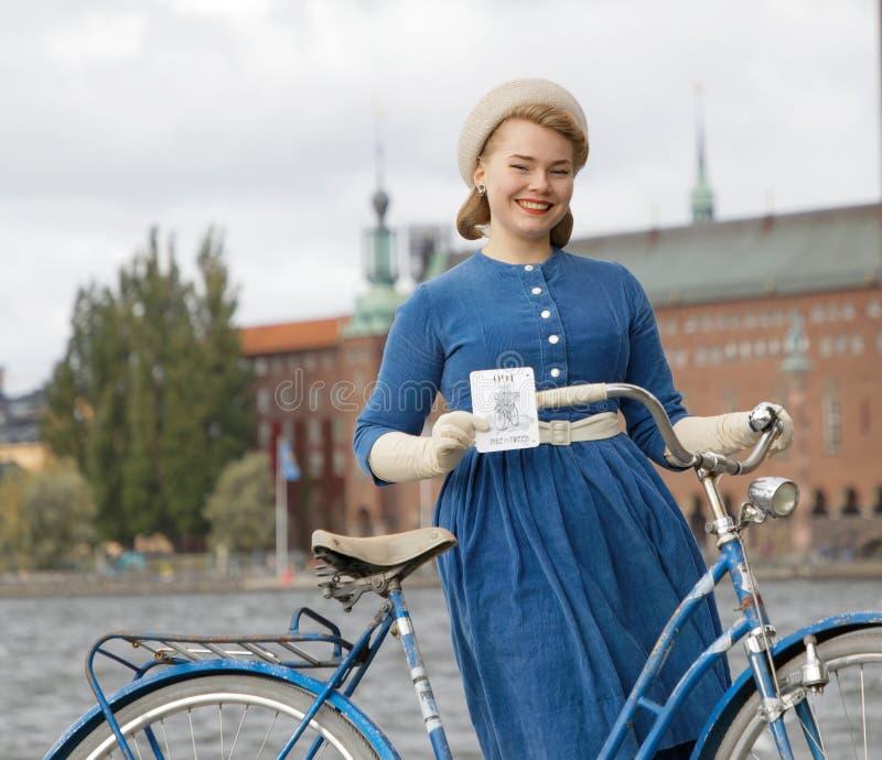 Closeup av den härliga le kvinnan som bär den gammalmodiga blåa klänningen som framme rymmer en retro cykel av det Stockholm stad royaltyfri foto