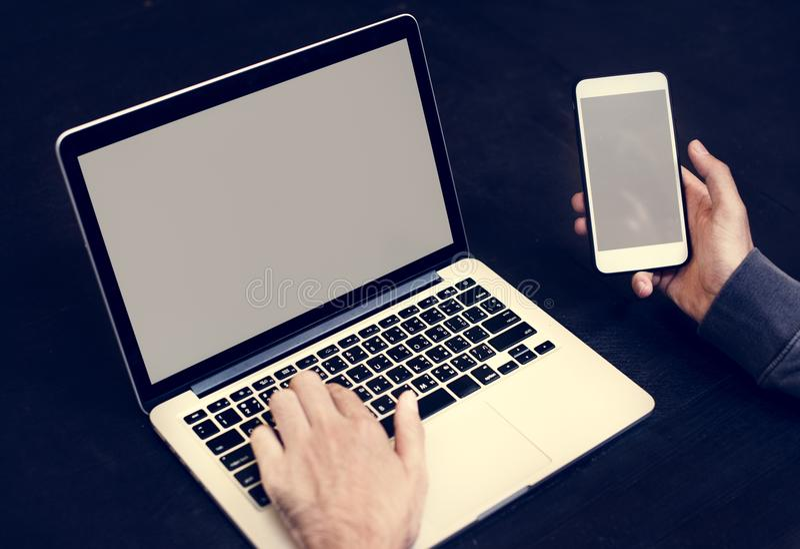 Closeup av den hållande mobiltelefonen för hand med datorbärbar datorbakgrund royaltyfri foto