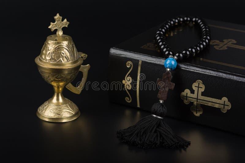 Closeup av den heliga bibeln, radbandpärlor med korset och rökelsegasbrännare på svart bakgrund Religionbegrepp och tro royaltyfri fotografi