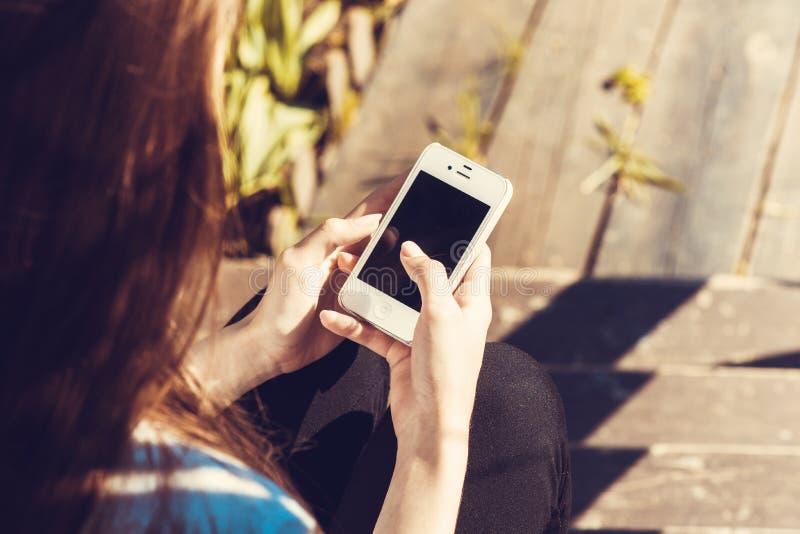 Closeup av den kvinnliga handen genom att använda en smart telefon royaltyfri fotografi
