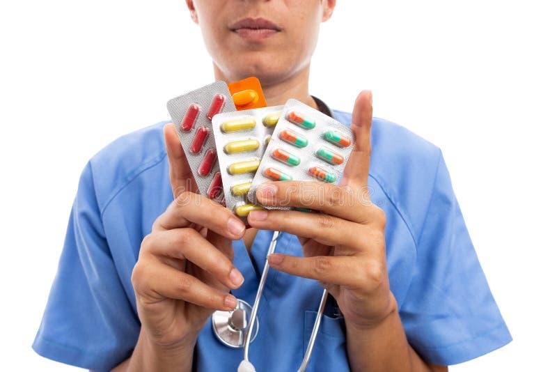 Closeup av den kvinnliga sjuksköterskan eller doktorn som rymmer färgrika preventivpillerminnestavlor royaltyfri bild