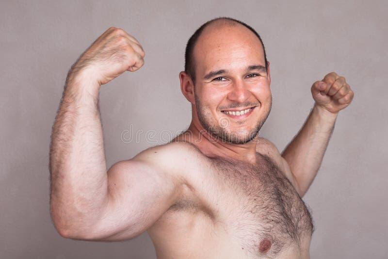 Closeup av den lyckliga nakna mannen som visar hans starka armar royaltyfri fotografi
