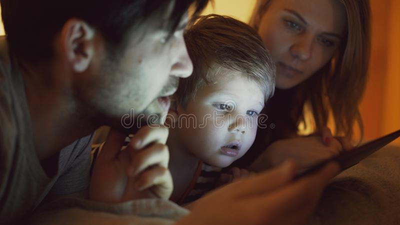 Closeup av den lyckliga unga familjen som hemma ligger i säng medan pys som lär att spela den digitala minnestavladatoren för fotografering för bildbyråer