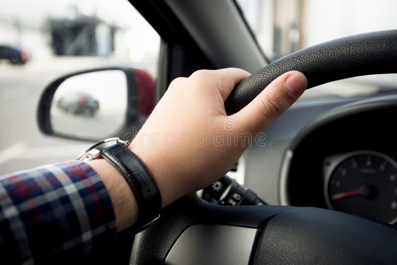 Closeup av den manliga handen i klockor som rymmer bilstyrninghjulet royaltyfri foto