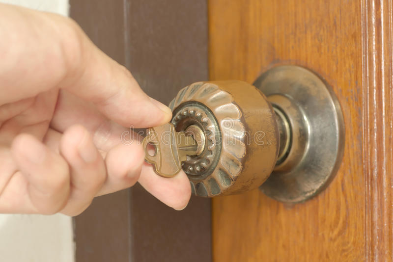 Closeup av den manliga handen som låser den gamla dörren upp royaltyfri foto